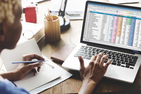 man on laptop looking at spreadsheet